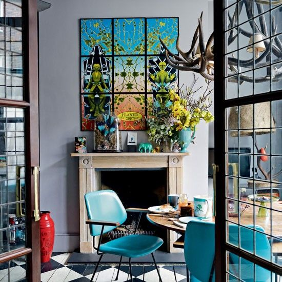 Statement pieces, such as the antler chandelier, Gilbert & George print and turquoise dining chairs stand out against the elegant grey walls.