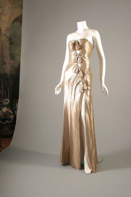 DIOR by John Galliano, Golden lamé evening  sheath, S/S 2003.  Worn by Laetitia Casta at the Cannes Film Festival.  Available US Size 6.