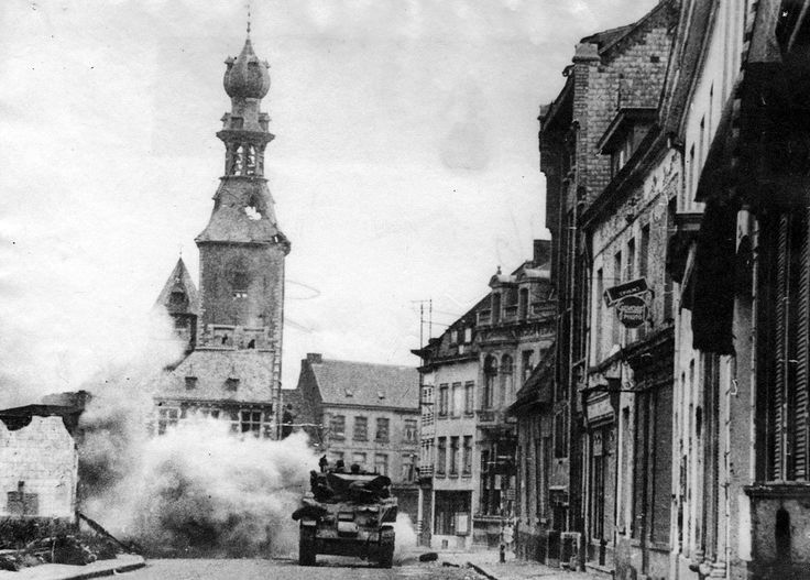 Tanks of the 1st Polish Armoured Division enter the town of Tielt, in West Flanders, under artillery fire. In the background the 'Halletoren'.
