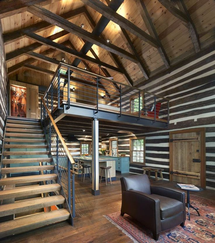 Steel I-beams allow for as much clear space beneath the bedroom as possible. The fabricated steel has a rawness that complements the hewn logs. The steel railing, which mirrors the chinking in the walls, is a reinterpretation of local cattle gates. Cherry is used as stair treads and post inserts.
