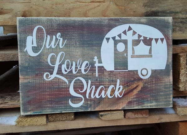 "This rustic 12"" x 7.5"" wooden sign is an adorable and whimsical addition to your love shack! A unique weathered background with hints of grey, blue, burgundy and green with white lettering and design."