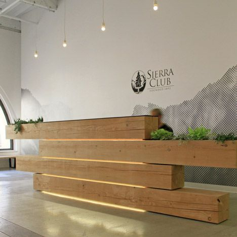 A plant-filled stack of timber beams forms the reception desk of an environmental association's headquarters in San Francisco; Sierra Club. Love this!