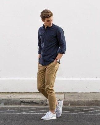 Ponte una camisa de manga larga azul marino y un pantalón chino marrón claro para un almuerzo en domingo con amigos. Deportivas grises añadirán un nuevo toque a un estilo que de lo contrario es clásico.