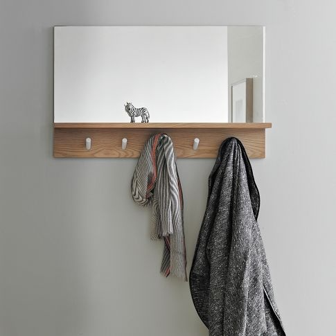 """West Elm   Exit strategy. This simple entryway mirror features a shallow shelf to store keys, pegs to hang coats and a mirror to consult on the way out the door. An all-in-one system that's great for small spaces. • Mirror; engineered wood with barley-stained finish. • 34""""w x 21.5""""d x 5.75""""h. $199"""