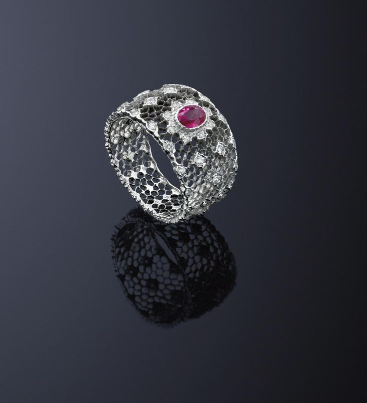 A ruby and diamond ring, by Buccellati  The pierced openwork honeycomb band set to the centre with a oval ruby and circular cut diamond cluster, and decorated with similarly cut diamond accents, ring size L ½, signed 'Buccellati'.