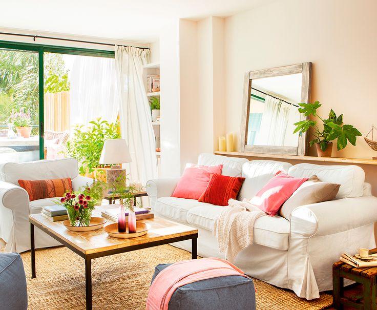 Salón con con salida a la terraza con sofá blanco, alfombra de fibras y espejo apoyado sobre el estante