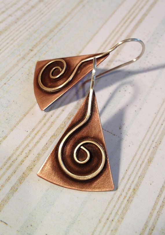 I created these earrings by soldering a hand made sterling silver spiral on to a copper triangle. The spiral design continues on to become the ear