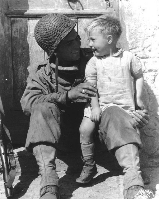 Pvt Fred Lindin US Army with a young boy, France 1944. 2nd Infantry Division