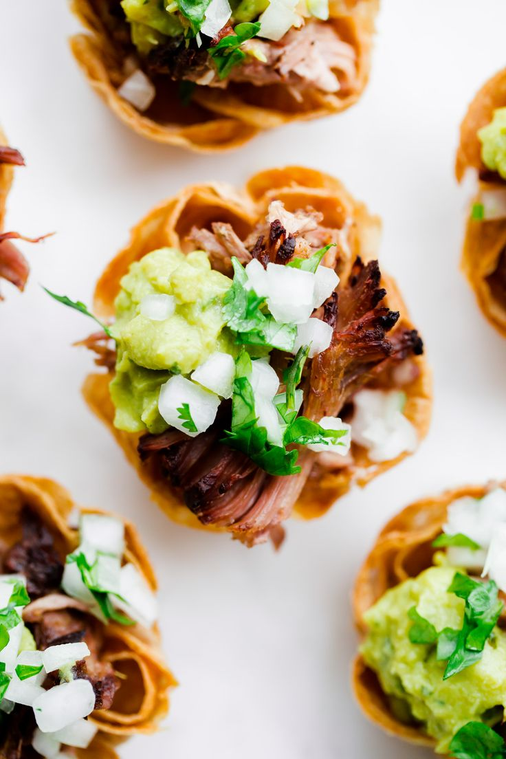 Slow cooker carnitas taco bites - homemade mini tortilla cups filled with pork carnitas and topped with guacamole, onion, and cilantro! Perfect for game day.