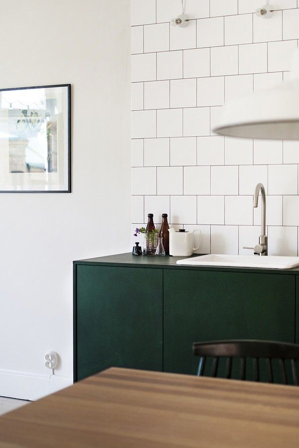 Square white tile backsplash; dark green cabinets