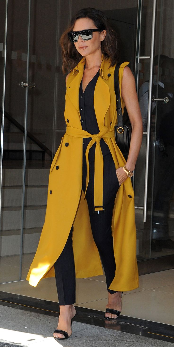 Victoria Beckham in a yellow sleeveless trench, completed with black shades and sandals. .
