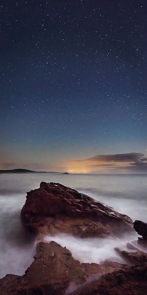 Photographed by Andrew Carter - i like how the stars stand out using long exposure, which has also created a haze effect on the water
