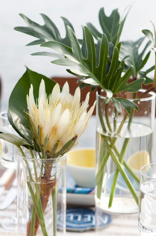 Centerpieces made of flowers indigenous to Hawaii: pincushion protea, lotus pods and a mix of tropical leaves