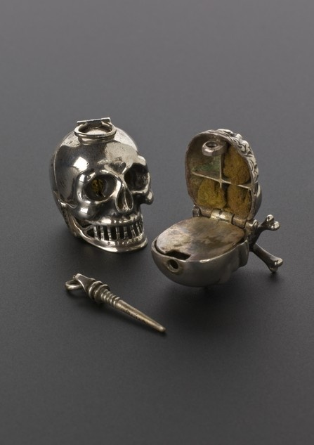 Silver Skull Vinaigrette, Europe 1701-1900: Used to hold strong smelling substances to be sniffed via tiny holes when the user was passing a particularly smelly area. At the time miasma theories of disease were dominant (the idea foul air caused disease), so carrying a vinaigrette was a protective measure. If a person felt faint they could sniff the vinaigrette & the sharp smell was hoped to shock the body into action. The skull was a memento mori- a reminder of death & was carried at all…