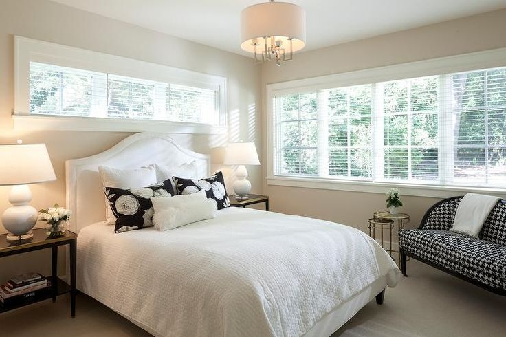Exquisite black and white bedroom features a cream walls framing a long window dressed in blinds positioned over a white camelback headboard located behind a bed dressed in white bedding topped in black and white rose pillows placed behind white lumbar pillow.