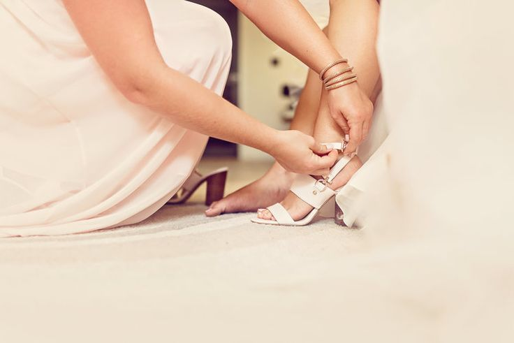 Your bridesmaids will be happy to help you tie up your shoes on wedding day | Bride nude Coach sandals | Bridal Suite at wedding venue | Photography: Melissa Avey