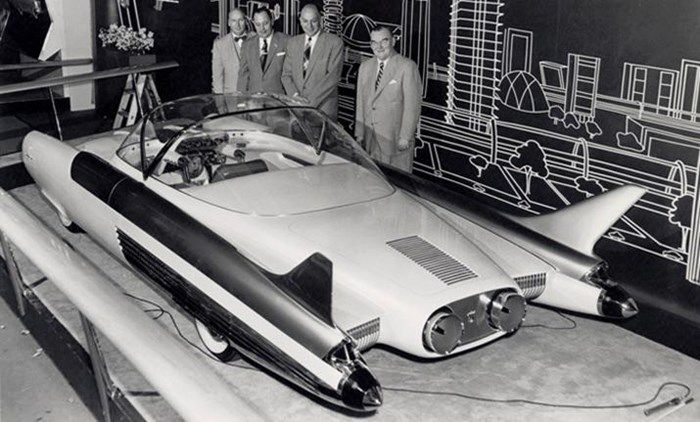 "Appearing at the 1954 Chicago Auto Show, the FX-Atmos featured a glass dome roof, tail fins, rocket exhaust taillights and needle-like radio antennae protruding from front fender pods. The radical cockpit had a center-mounted driver's seat and two-passenger rear seats. Dual handgrips replaced the normal steering wheel and the dash-mounted ""Roadarscope"" radar screen provided highway information."