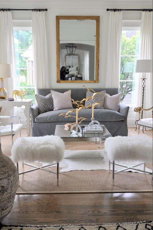Pastel toned living room with gold leaf mirror, white cowhide over sisal rug, white shag ottoman - sophisticated.