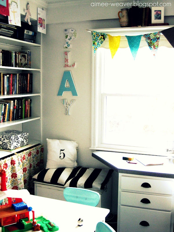 office/playroom. shelf over window with bunting.