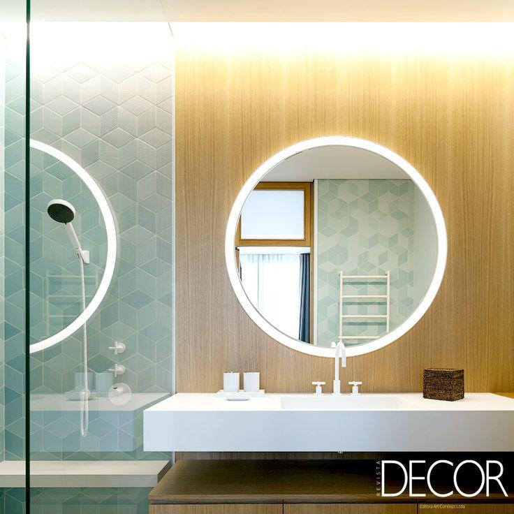 Madeira, espelho circular, revestimento com textura geométrica e tonalidade branca compõem este elegante espaço íntimo