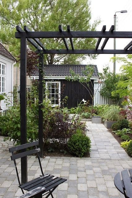 Pergola painted black in a contemporary garden set-up....
