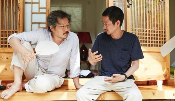 """Director Hong Sang-soo, left, and Japanese actor Ryo Kase chat on the film set of """"Hill of Freedom"""" (2014)"""