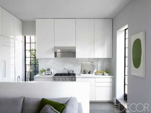 In this New York City home high above the city, the kitchen's lacquer cabinetry is custom made for a clean, modern aesthetic. It is echoed in style by the backsplash and countertop, made with Calacatta marble. The range is by Viking, the refrigerator is by Sub-Zero and the print is by Ellsworth Kelly.