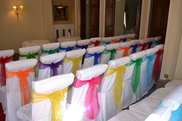 Rainbow Coloured Organza Bows on White Chair Covers