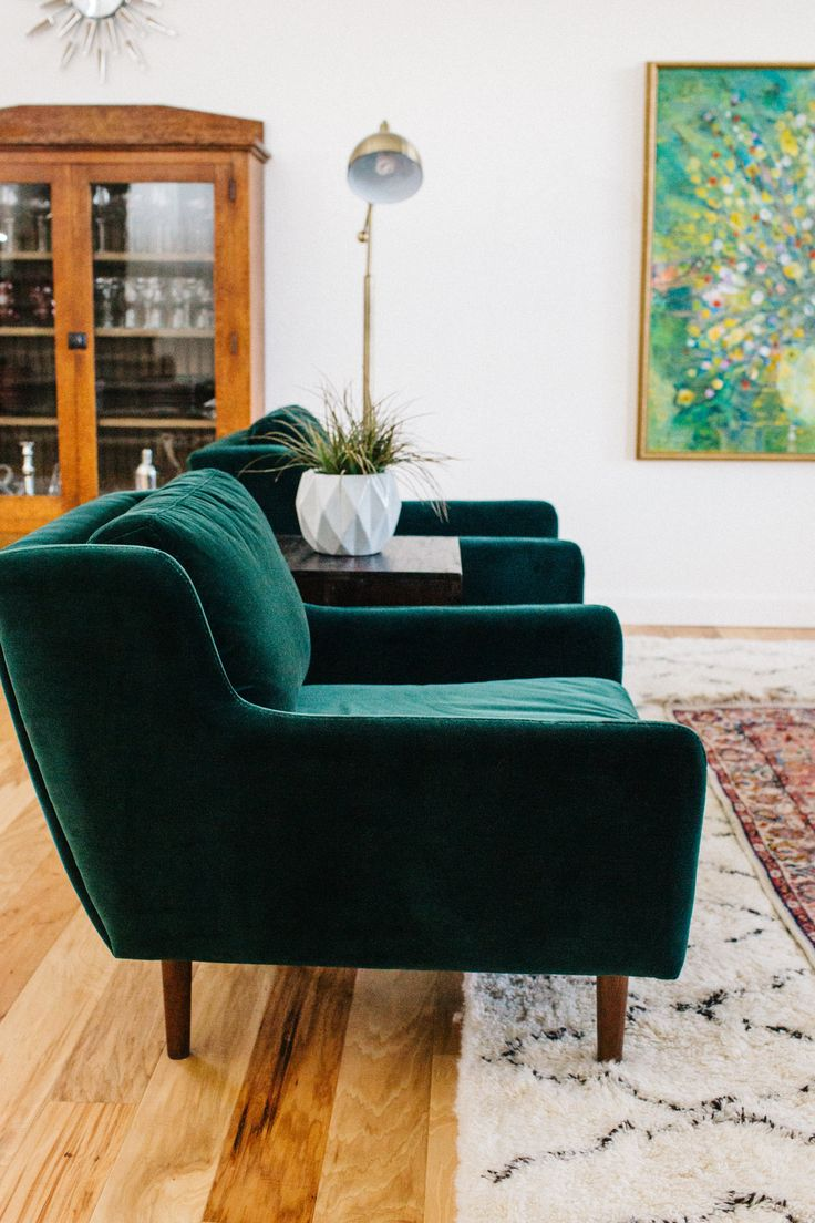 a pair of green velvet chairs with modern lines