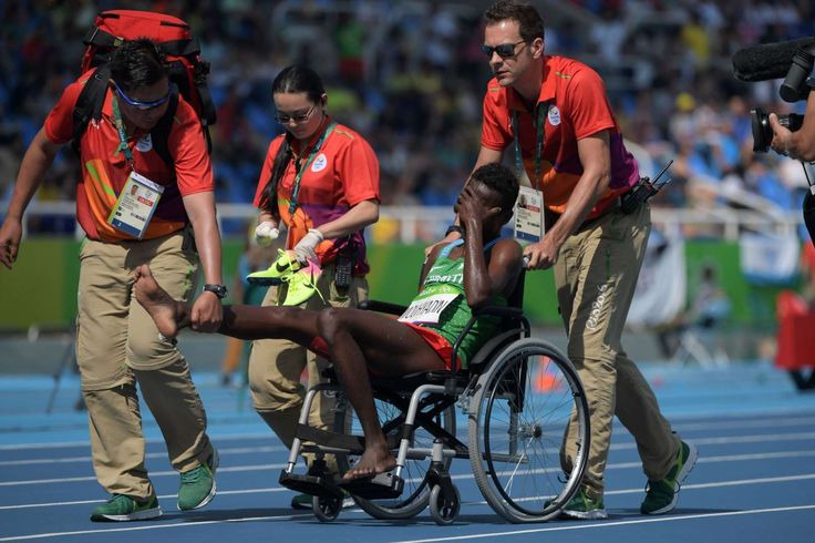 Abdi Waiss Mouhyadin of Djibouti is helped off the track during the men's 1500 preliminaries in the Rio 2016 Summer Olympic Games at Estadio Olimpico Joao Havelange.
