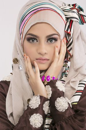 Create a bow by layering a colourful ribbon/band on top of a pastel coloured hijab for a soft, girly look