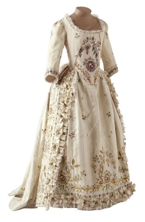 """Ballgown, 1780-85 France, Musée des Tissus de Lyon    This dress, also called """"robe parée"""", is a ball dress. The skirt is worn over a pannier which, early 1780, was less ample than the one used under the dress """"à la française"""". The decoration consists of appliqué painted flowers, gauze flounces and extremely refined embroideries. It exemplifies the dresses Rose Bertin, Marie-Antoinette's dressmaker, used to create for the queen."""