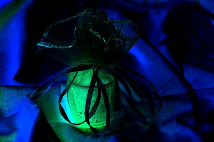 Green-Glowing Candle in a Sea of Blue Satin by amecylia
