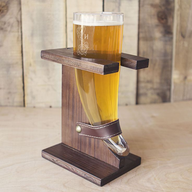 Feel like a viking when your drink with this unique beer glass. The novelty glass features a classic viking horn shape, and rests in a rustic wooden stand with a leather strap. The glass is engraved w