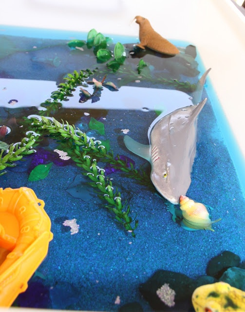 """Under the sea - sea creatures, sand, blue water, stones, shells, a boat & fake fish tank plants ("""",)"""