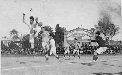 24 de febrero de 1918 en el terreno de la Enramadilla y que terminó con victoria del Real Betis por 3 a 1 frente al Sevilla FC. En el fondo, perspectiva frontal de la fábrica de losetas de cemento.