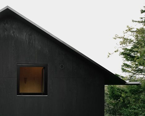 """Striking black house. """"cladded in plywood, coated in black pine tar just like the traditional way of preserving wooden boats."""""""