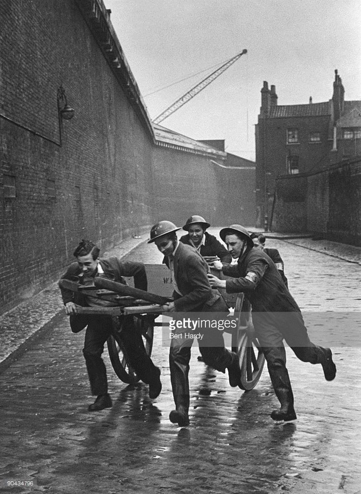 A fire squad rushes along a dock wall in the East End of London to the scene of a fire after an air raid during the Blitz, April 1941. The group are members of the 'Dead End Kids' - a gang of teenage boys from the East End of London, who work as unofficial fire fighters. Original publication: Picture Post - 721 - Dead End Kids - unpub.