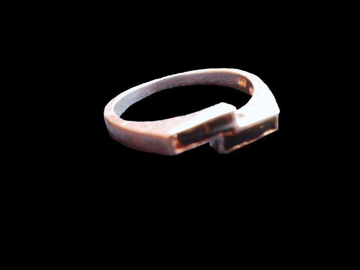 Delicado anillo en plata, con decoración de dos piedras delgadas y rectangulares en color negro unidas paralelamente por los extremos
