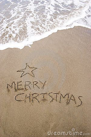 Merry Christmas written in sand on the beach.