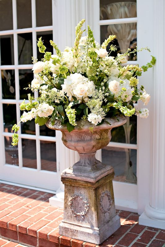 Ceremony Decor: Flowers at beginning of aisle and at altar.    I would like to have 2-4 arrangements like this. I would like large urns lining the entrance of the aisle and also by the altar. This arrangement is beautiful but would be nice to add some pink and peach flowers in it.