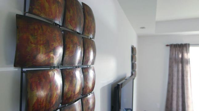 AVANT : Les deux éléments décoratifs de chaque côté du téléviseur seront retirés. Sur la droite on pourra retrouver des tablettes de métal et des paniers grillagés pour accueillir les accessoires décoratifs, et tout au haut et à gauche du téléviseur, des cadres photos seront installés pour le ceinturer et le faire disparaître davantage.