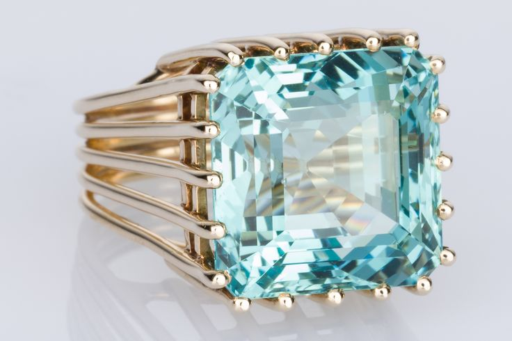 The Sea of Love - a magnificent blue/green Aquamarine weighing an incredible 21cts. This gemstone has to be seen to be believed - the faceting, the depth of colour it's truly a one-of-a-kind ring with its 14k yellow gold cage holding this magnificent gem. Love It?  It's for sale on www.1stdibs.com - The Jewellery Trading Company - Hurry it won't last long!