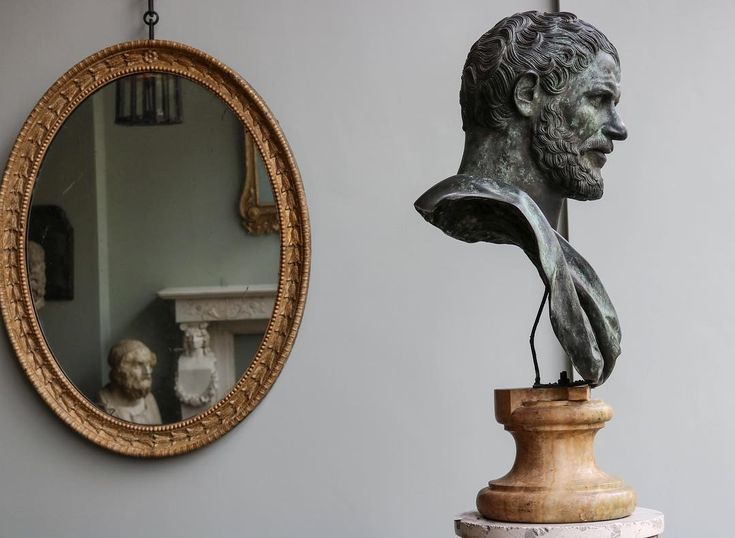 A late C19th exceptional quality bronze bust of Demosthenes almost certainly by the Chiurazzi foundry in Naples supported on a contemporary turned alabaster socle with a George III carved giltwood wall mirror with bell flowers and beaded border. #jamb #antiques #sculpture #mirrors #craftsmanship #englishcountryhouseaesthetic #london #pimlicoroad