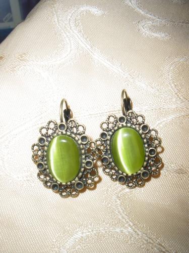 Handgefertigte Ohrringe mit grünem Stein in einem bronzenen Ohrring.
