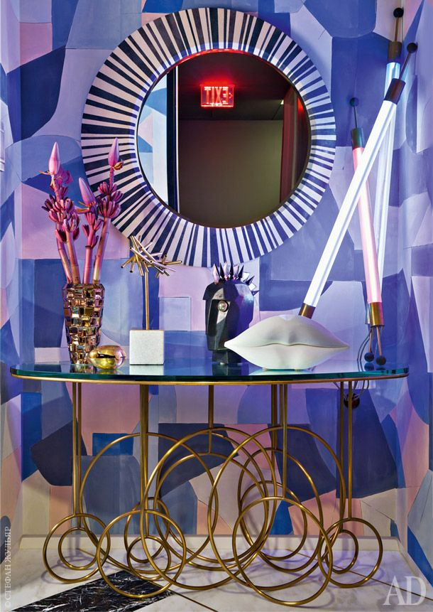 Over the top vignette by Kelly Wearstler with show-stealing wallpaper, some of her signature sculptures, neon lights & vintage mirror