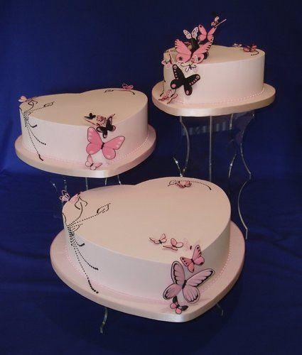 Three tier white wedding cake with multi hued pink sugar butterflies