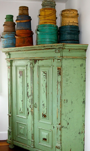 Colorful buckets and old light green cabinet.