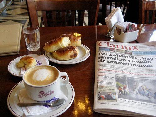 """Desayuno tradicional. Cafe con leche y medias lunas leyendo """"El Clarin"""""""