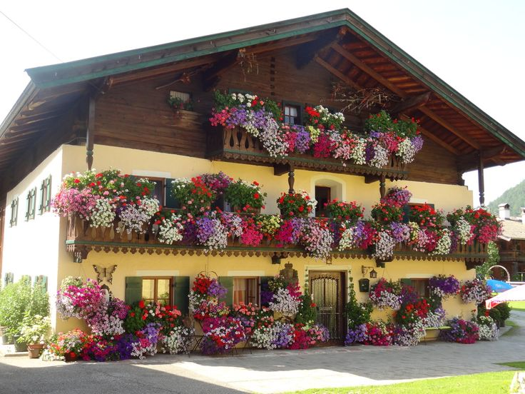 Blumenhaus St.Martin, Salzburg, Austria. ~ So beautiful! I know many other very similar houses throughout Austria. It's their joy to decorate like this every summer!